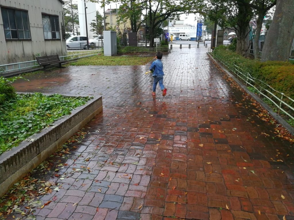 傘を振り回しながら走るたっくん